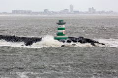 Dutch pier IJmuiden with lighthouse and stormy sea royalty free stock image