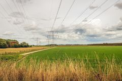 Dutch polder landscape with high voltages lines. And power pylons. The photo was taken near the village of Zevenbergen, North Brabant, on a cloudy day in stock photography