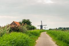 Dutch polder landscape with windmills. Picturesque polder landscape near the village of Sleeuwijk in the Netherlands. A narrow path leads to an ancient hollow royalty free stock image
