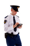 Dutch police officer filling out parking ticket. Royalty Free Stock Images