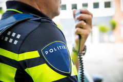 Dutch policeman with radio focus on badge with logo Royalty Free Stock Photography