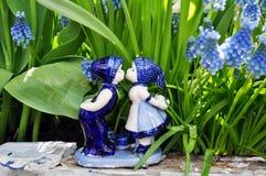 Dutch porcelain boy kissing girl. Traditional blue porcelain boy kissing girl on plants background Stock Photo