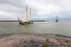 Dutch sailing ships entering Harlingen Harbour in The Netherlands. Dutch sailing ships on the Wadden Sea entering Harlingen Harbour in The Netherlands against a Stock Photo