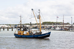 Dutch shrimper sails into the harbour of Lauwersoog. Lauwersoog is the home port of many trawling fleets and in addition to the  fish auction, it also Stock Photos