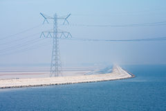 Dutch snowy dike disappearing in winter haze Stock Photos