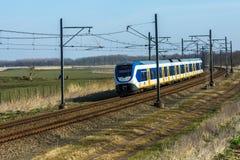 Dutch sprinter train traveling through countryside. Flevoland, the Netherlands - March 26, 2016: Dutch sprinter train traveling through countryside Stock Images