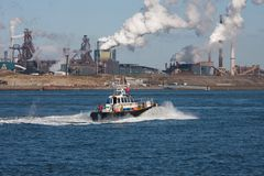 Dutch steel factory along the coast with motorboat Stock Photo