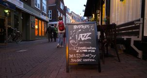 Dutch street with Haarlem Jazz and more signs. Haarlem, Netherlands - Circa 2018: Pedestrians walking at dusk on the tiny Dutch street with Haarlem Jazz and more stock video footage