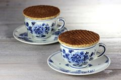 Dutch syrup waffles. Traditional Dutch syrup waffles with Delftware on wooden background Royalty Free Stock Photography