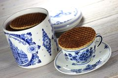 Dutch syrup waffles. Traditional Dutch syrup waffles with Delftware on wooden background Royalty Free Stock Image