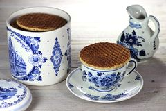 Dutch syrup waffles. Traditional Dutch syrup waffles with Delftware on wooden background Royalty Free Stock Photo