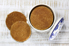 Dutch syrup waffles. Traditional Dutch syrup waffles in an original Delftware container on wooden background Stock Images