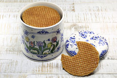 Dutch syrup waffles. Traditional Dutch syrup waffles in an original Delftware container on wooden background Stock Image
