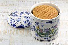 Dutch syrup waffles. Traditional Dutch syrup waffles in an original Delftware container on wooden background Stock Photography