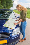 Dutch teenage girl reads road map on car hood royalty free stock images