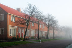 Dutch terraced houses. Typical row of terraced red brick houses in a dutch street of a small village. Photo taken on a misty morning stock photo