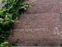 Text wall. Dutch text on a brick wall with bushes Royalty Free Stock Photography