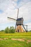 Dutch thatched stone hollow post mill with wooden upper house or Stock Image