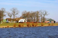 Dutch farm house buildings rural canal water, Netherlands. Dutch traditional farm house buildings with thatch roofs along the water in rural landscapes Royalty Free Stock Photography