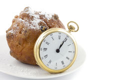 Dutch traditionally oliebol and pocket watch Royalty Free Stock Images