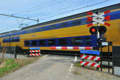 Dutch train. Fast speeding dutch train with motion blur and closed barrier and red warning signal Stock Images