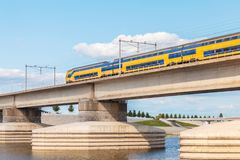Dutch train crossing the sideskirts of the river Waal in front o Stock Photography