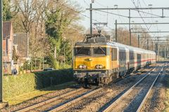 Dutch train locomotive with germand wagons passing the village during wintertime. Twelllo, the Netherlands, December 17th 2017: Dutch train locomotive with Stock Images