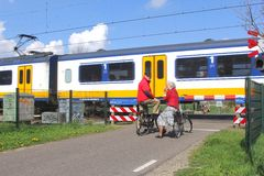 Senior couple waits while a Dutch sprinter train is passing at the railway crossing, Netherlands Royalty Free Stock Image