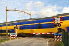 Dutch train passing a railway crossing. Dutch yellow and blue intercity high speed train passing a railway crossing with the barrier down and flashing warning Stock Photos