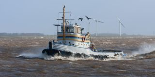Dutch tugboat sailing with high waves Stock Image