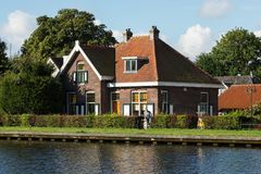 Free Dutch Typical Houses By The River Bank Royalty Free Stock Photography - 104047807
