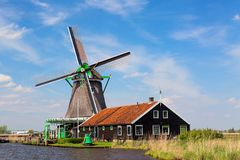 Dutch typical landscape. Traditional old dutch windmill with house blue sky in the Zaanse Schans village, Netherlands. Famous tour. Ism place stock photos