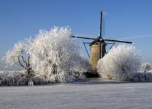 Dutch view. A photo of a dutch windmill with a frozen river in front royalty free stock photography