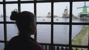 Dutch village on the rewerbank. Young woman opposite window looking at typical holland landscape dutch village on the rewerbank with old-fashioned windmills stock video