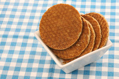 Dutch waffles in a white bowl. Called a stroopwafel isolated on a blue and white checkered table cloth Stock Photo