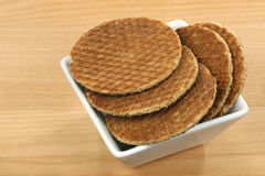 Dutch waffles in a white bowl. Called a stroopwafel in a white bowl on a wooden background Royalty Free Stock Photos