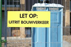 Dutch warning sign that says 'attention: exit construction traffic'. A yellow Dutch sign that warns people that this is an exit for construction and building Royalty Free Stock Photography