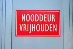 A dutch warning sign that says 'keep emergency door clear'. A red warning sign on a white door that says in Dutch to keep the emergency door free Stock Photo