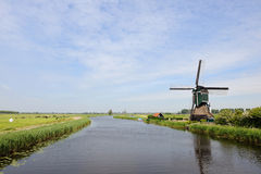The dutch wind mill horizon. Dutch wind mill near a river with blue skies Royalty Free Stock Image