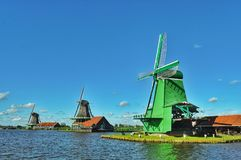 Dutch wind mill in Zaanse Schans. Dutch scenery with windmill of Zaanse Schans over river in a summer day stock photography