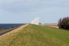 Dutch wind turbines along a straight dike Stock Photos