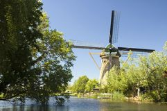 Dutch Windmill. Beautiful dutch windmill in front of a river. Taken with polarisation filter on a sunny day stock photos