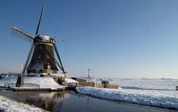 Dutch windmill. Surrounded by snow and ice on the canal Stock Image