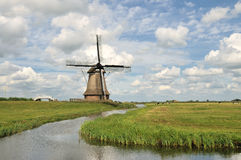 Dutch Windmill , Agricultural Building. With water, pasture and cloudy sky royalty free stock photos