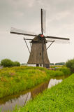 Dutch windmill along a reflecting ditch. Windmill De oude doorn (anno 1700) in the Dutch village of Almkerk Stock Photography