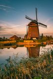 Dutch windmill along a river during the golden hour royalty free stock photography