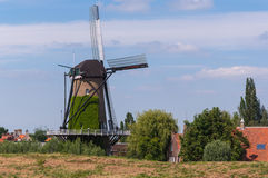 Dutch windmill behind a dike Stock Images