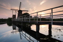 Dutch windmill with bridge in kinderdijk Royalty Free Stock Photography