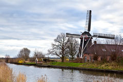 Dutch windmill by canal Royalty Free Stock Image