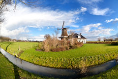 Dutch windmill by canal on green pasture Royalty Free Stock Photo